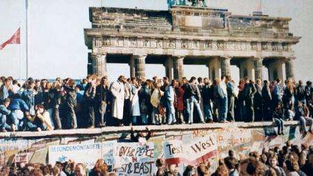 West and East Germans on top of the Berlin Wall at the Brandenburg Gate