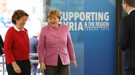"Angela Merkel walking with another woman in front of sign that says ""Supporting Syria and the Region - London 2016"""