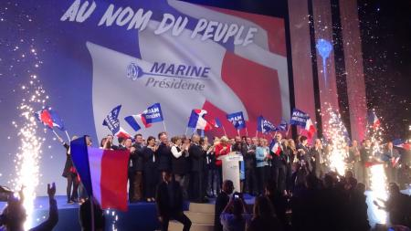 Marine le Pen surrounded by people and flags at a rally in Lille, France
