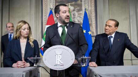 Matteo Salvini at a podium between Silvio Berlusconi and interpreter