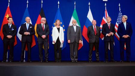 Foreign ministers announcing nuclear agreement in front of blue curtain and international flags