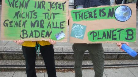 "Two people with cardboard signs that read ""There is no Planet B"" and ""wenn ihr jetzt nichts tut gehen wir alle baden"""
