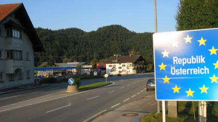 "Road at Austrian Schengen Border with blue sign that reads ""Republik Osterreich"" surrounded by EU's yellow stars"