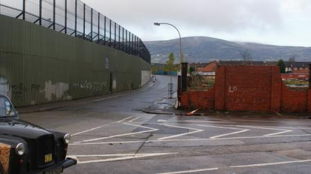 Belfast Peace wall, a high fence and cloudy skies