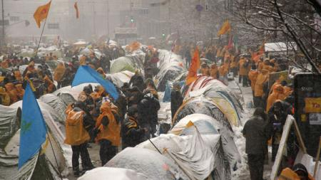 Tents and protestors in orange jackets covered in snow, flags surround them